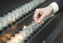 Hand lighting candle with long match in row of memorial candles (© Saul Loeb/AFP/Getty Images)