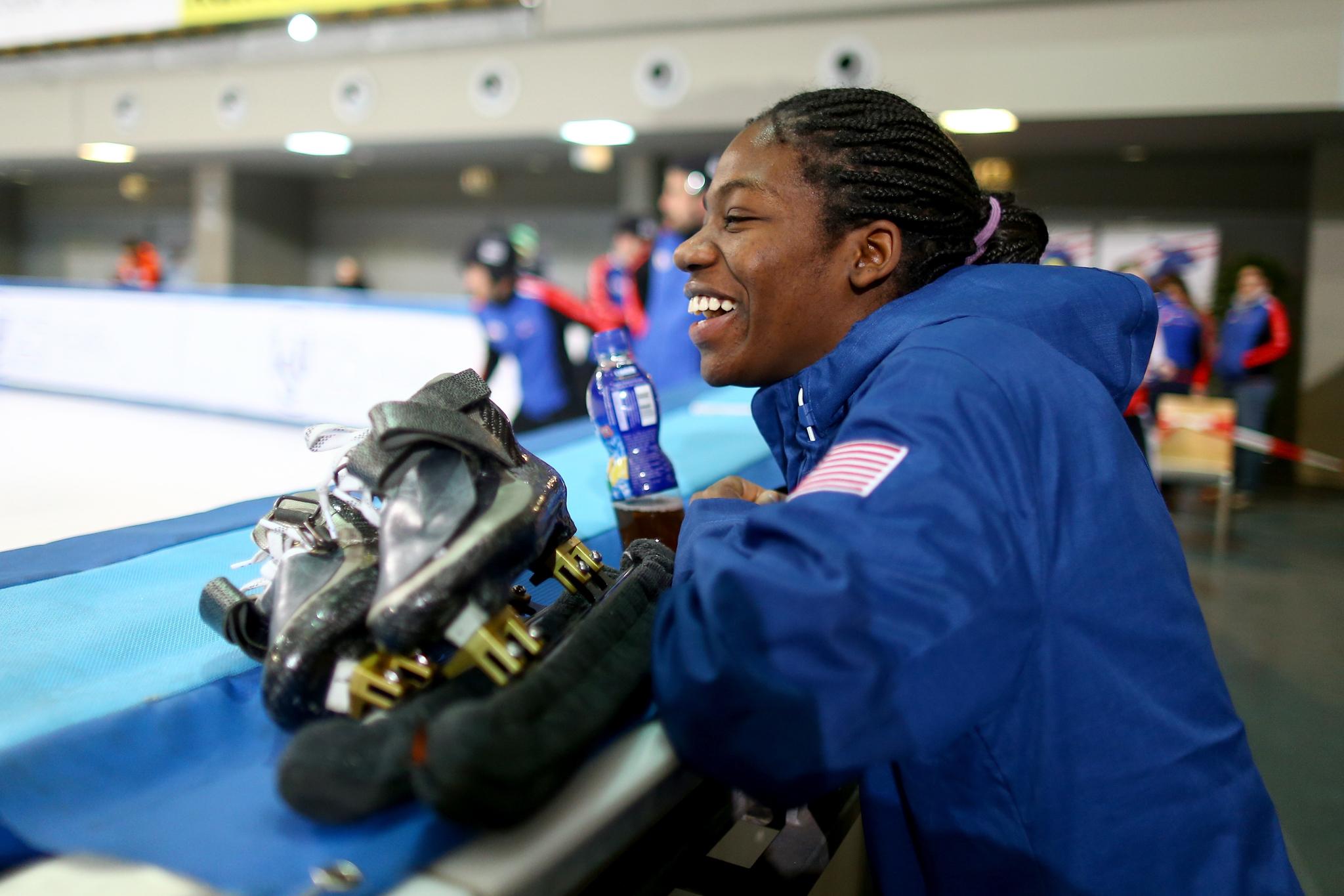 Maame Biney luce una chaqueta azul parada al borde de una pista de patinaje sobre hielo (© Christof Koepsel/ISU/Getty Images)