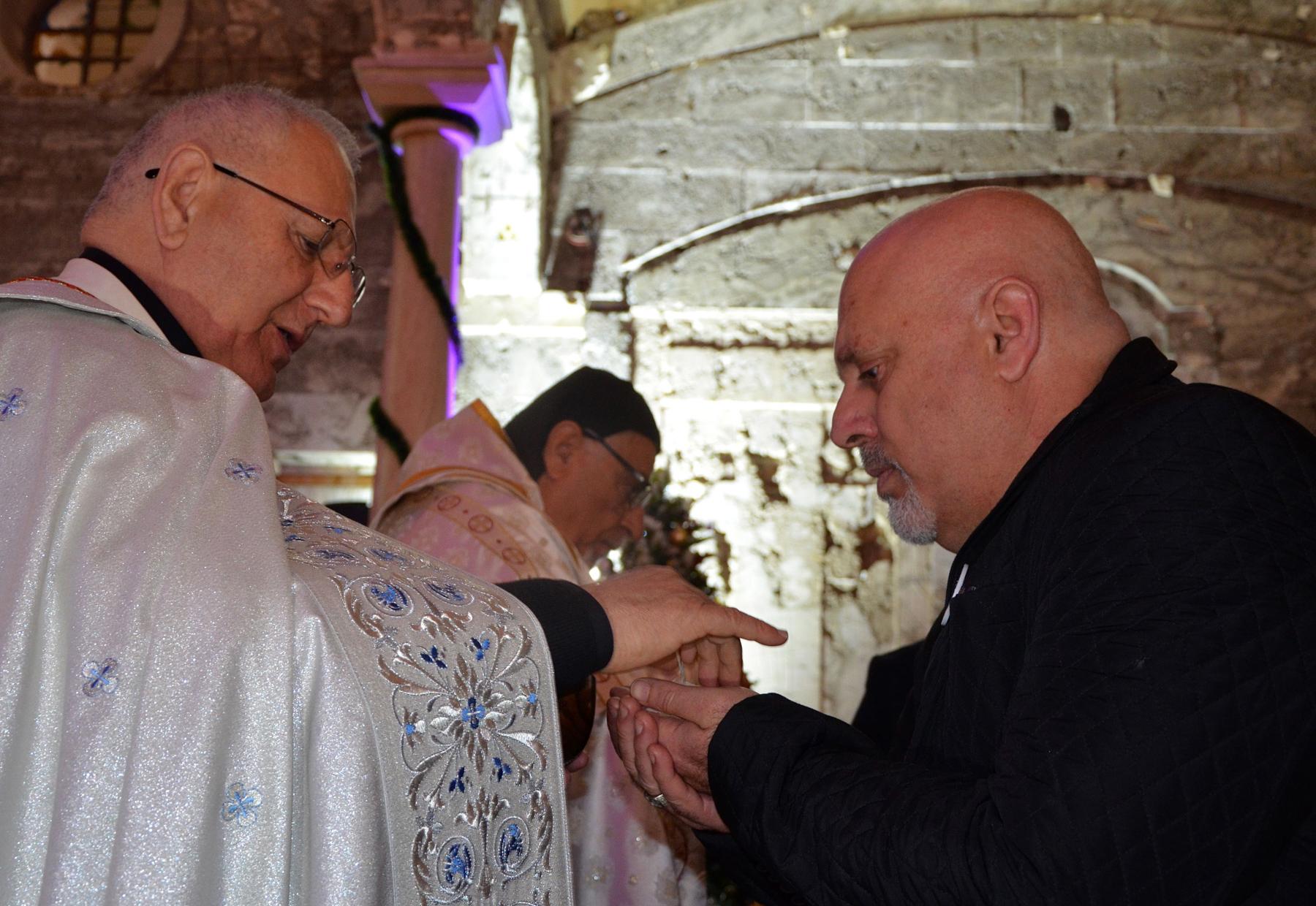 Un prêtre donne la communion à un fidèle (© Ahmad Muwafaq/AFP/Getty Images)