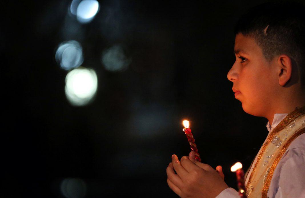 Un jeune garçon tenant une chandelle (© Safin Hamed/AFP/Getty Images)