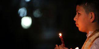 Boy holding candle (© Safin Hamed/AFP/Getty Images)