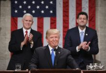 Le président Trump à un pupitre, avec Mike Pence et Paul Ryan en train d'applaudir derrière lui (© Win McNamee/Bloomberg/Getty Images)