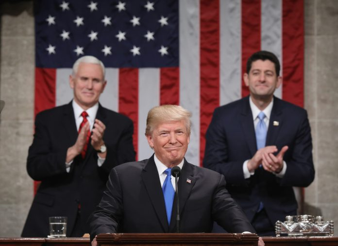 President Trump at lectern with Vice President Pence and Paul Ryan applauding behind him (© Win McNamee/Bloomberg/Getty Images)