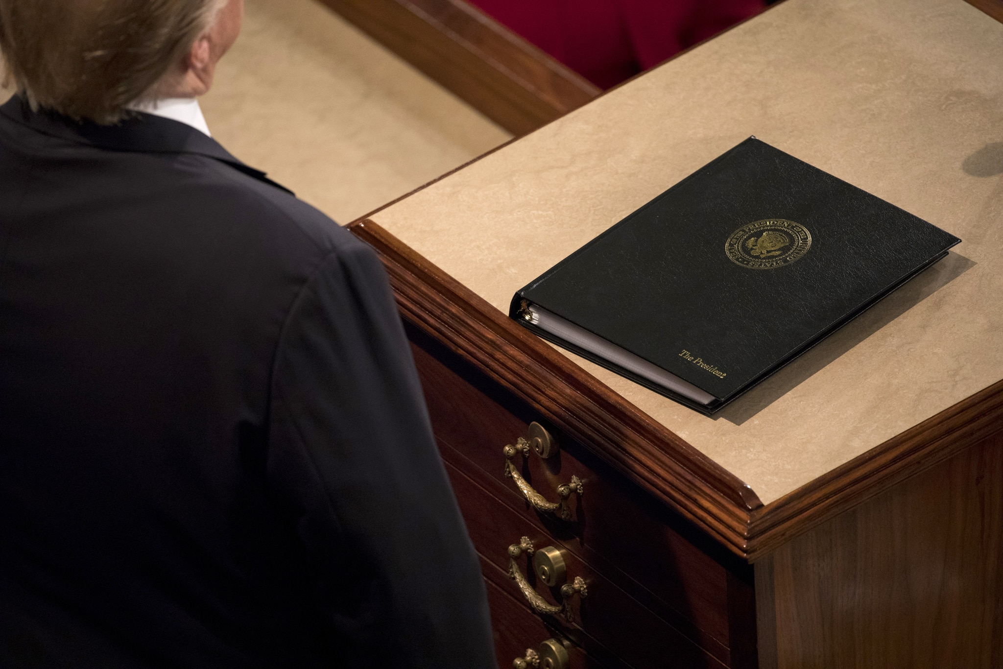 Person standing in front of binder on lectern (© Aaron P. Bernstein/Bloomberg/Getty Images)