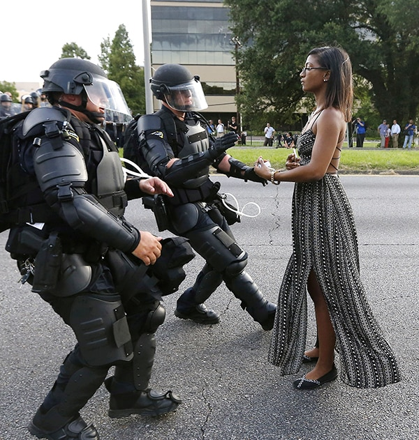 Woman in dress facing armored police (© Jonathan Bachman/Reuters)
