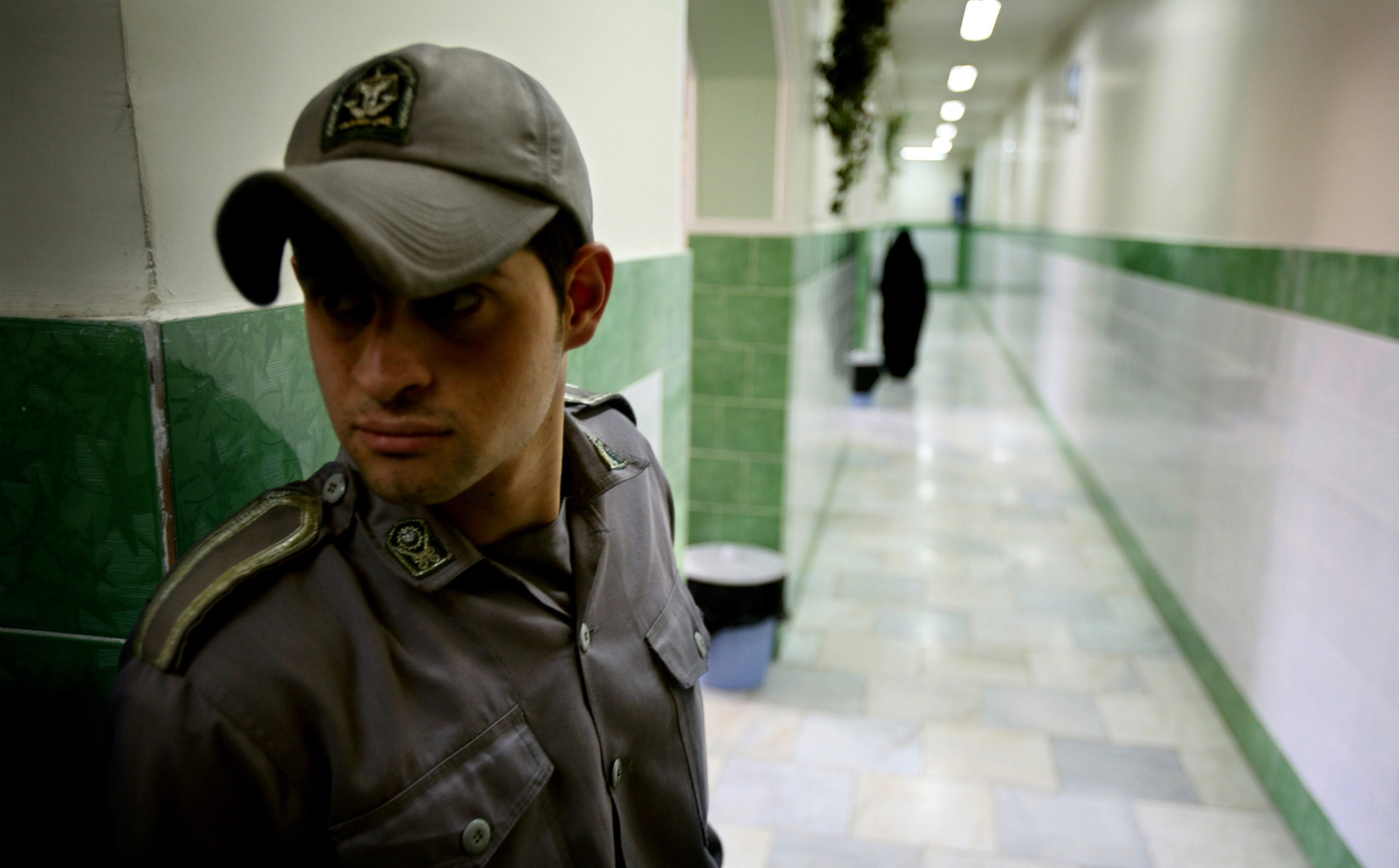 Young man in uniform with bill cap standing in a hallway (© Morteza Nikoubazl/Reuters)