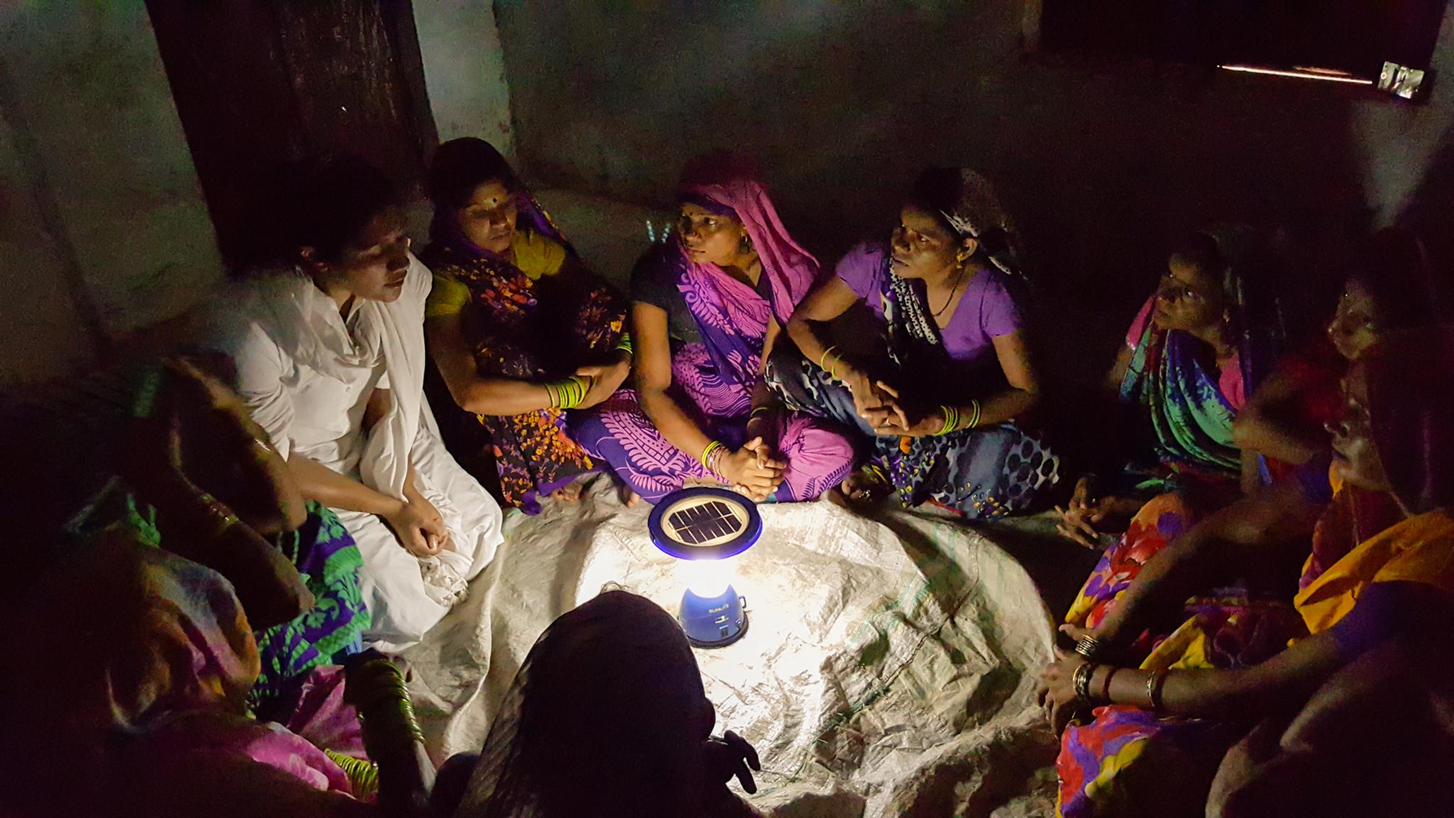 Women in India sitting around solar light (© Frontier Markets)