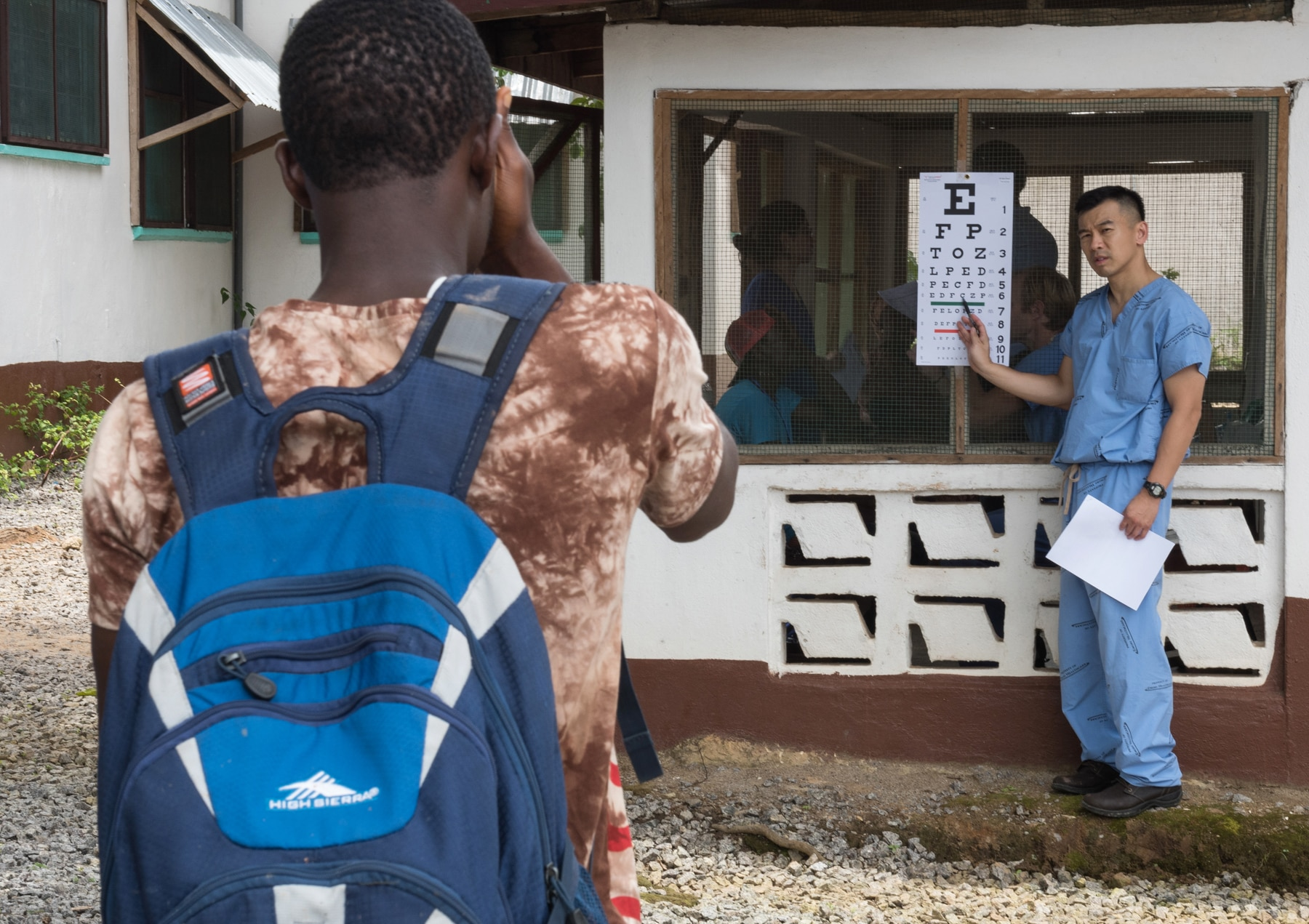 Young man looking at eye chart as man in blue scrubs points to line of letters (Joshua Yospyn/JSL)