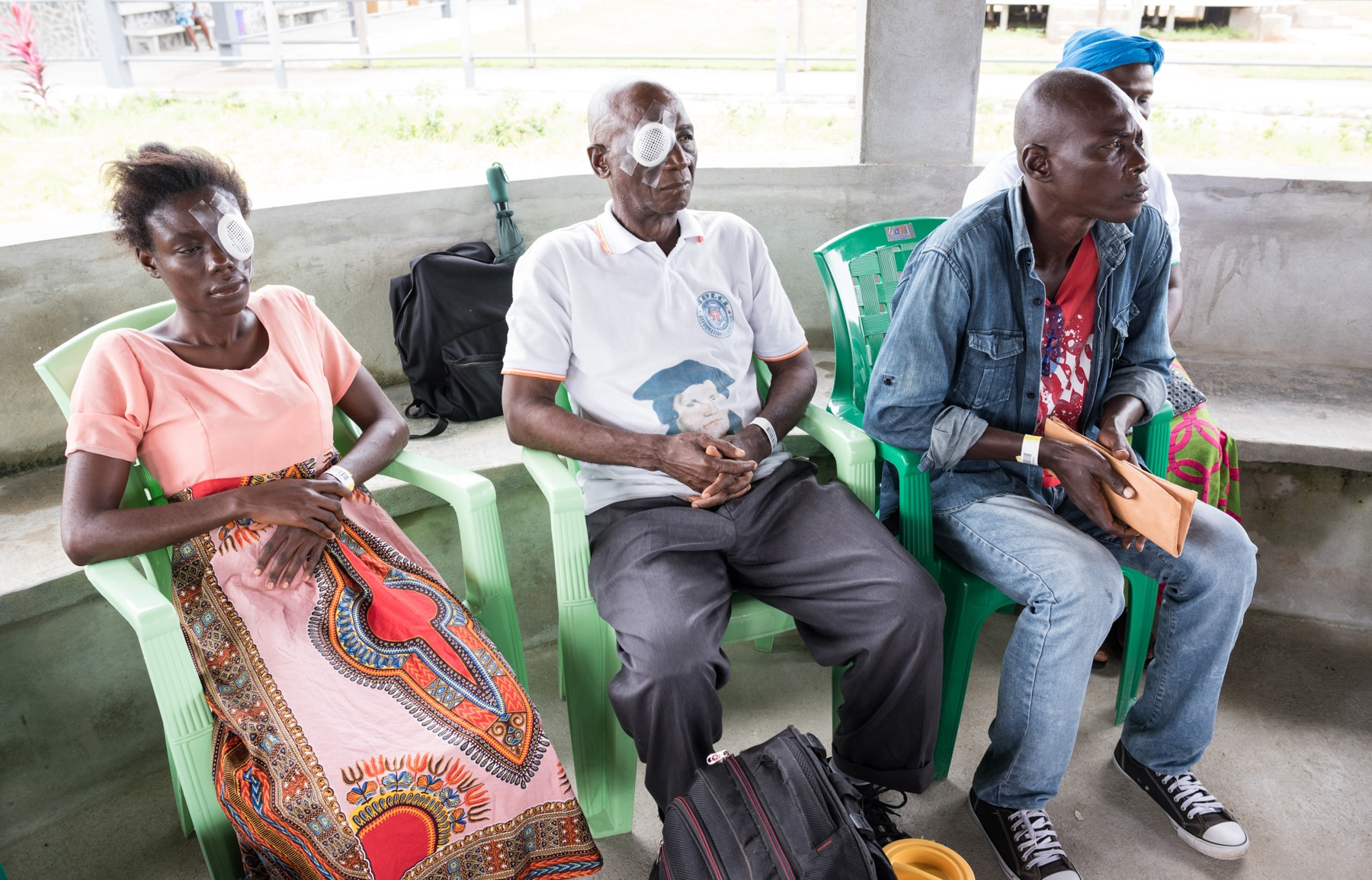 Three patients wearing eye patches sitting and waiting in open-air room (Joshua Yospyn/JSL)