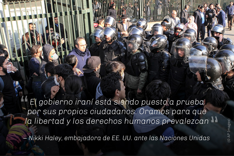Manifestantes frente a un grupo de hombres con cascos, y cita de Nikki Haley (© AP Images)