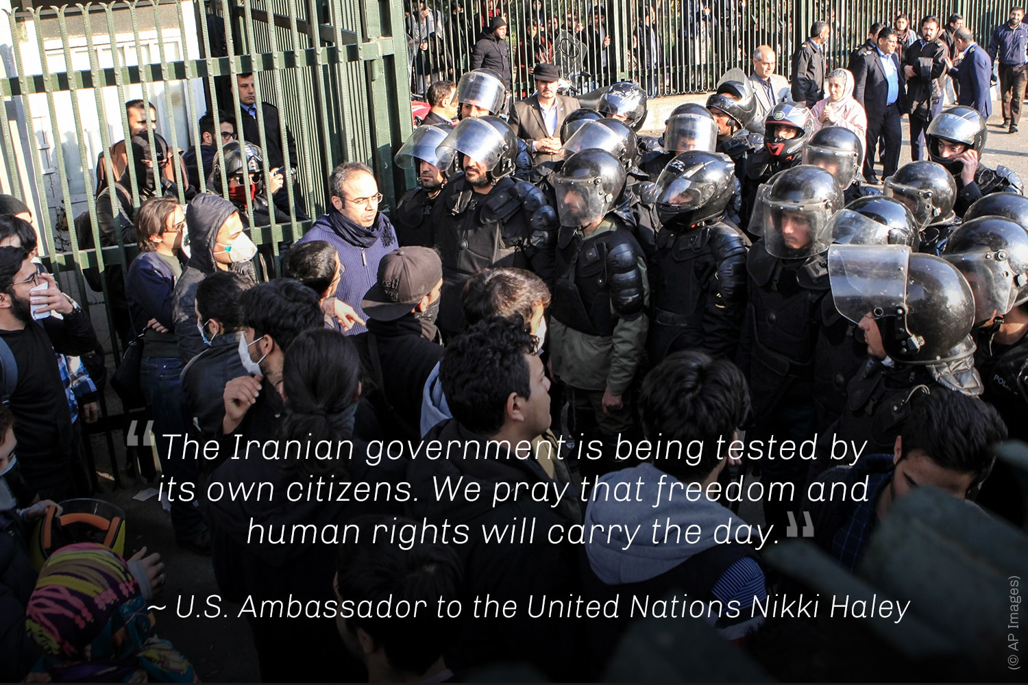 Demonstrators facing group of helmeted men, with Nikki Haley quote (© AP Images)