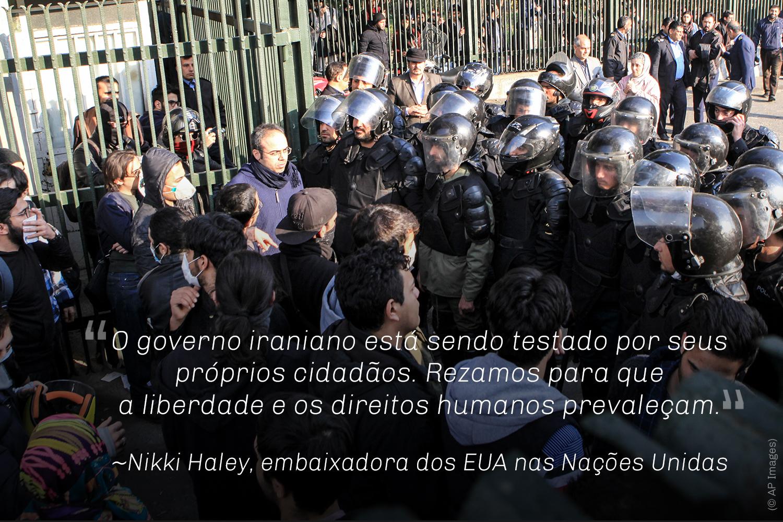 Manifestantes em frente a grupo de homens com capacetes. Citação de Nikki Haley (© AP Images)
