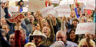 Crowd of people waving signs (© AP Images)