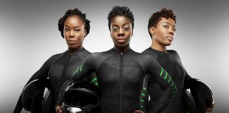 Three women wearing black body suits and holding helmets (© Obi Grant)