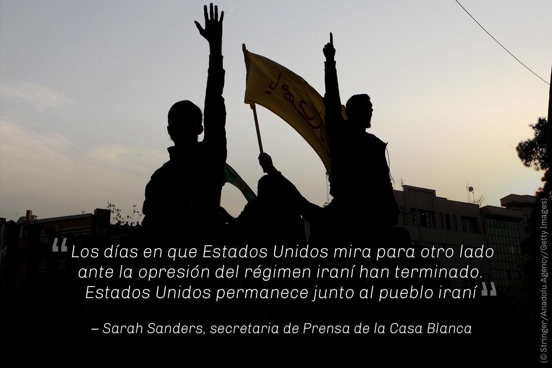 Silueta de manifestantes elevando los brazos y una pancarta, y cita de Sarah Sanders (© Stringer/Anadolou Agency/Getty Images)