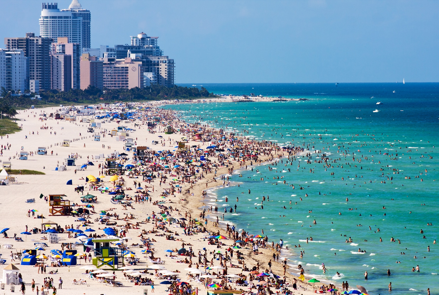 People sunbathing and swimming at beach, tall buildings in background (Shutterstock)