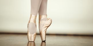 Ballerina standing on pointe in ballet shoes (Shutterstock)