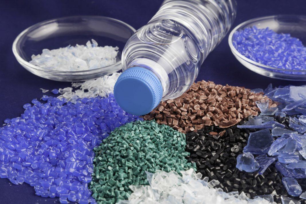 Montones de polímero de plástico de colores y una botella de agua (Shutterstock)