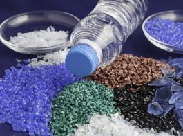 Piles of colored plastic polymers and a water bottle (Shutterstock)