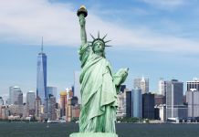 Statue of Liberty standing in front of city skyline (Shutterstock)