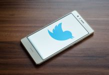 Mobile phone showing blue Twitter logo on screen (© Shutterstock)
