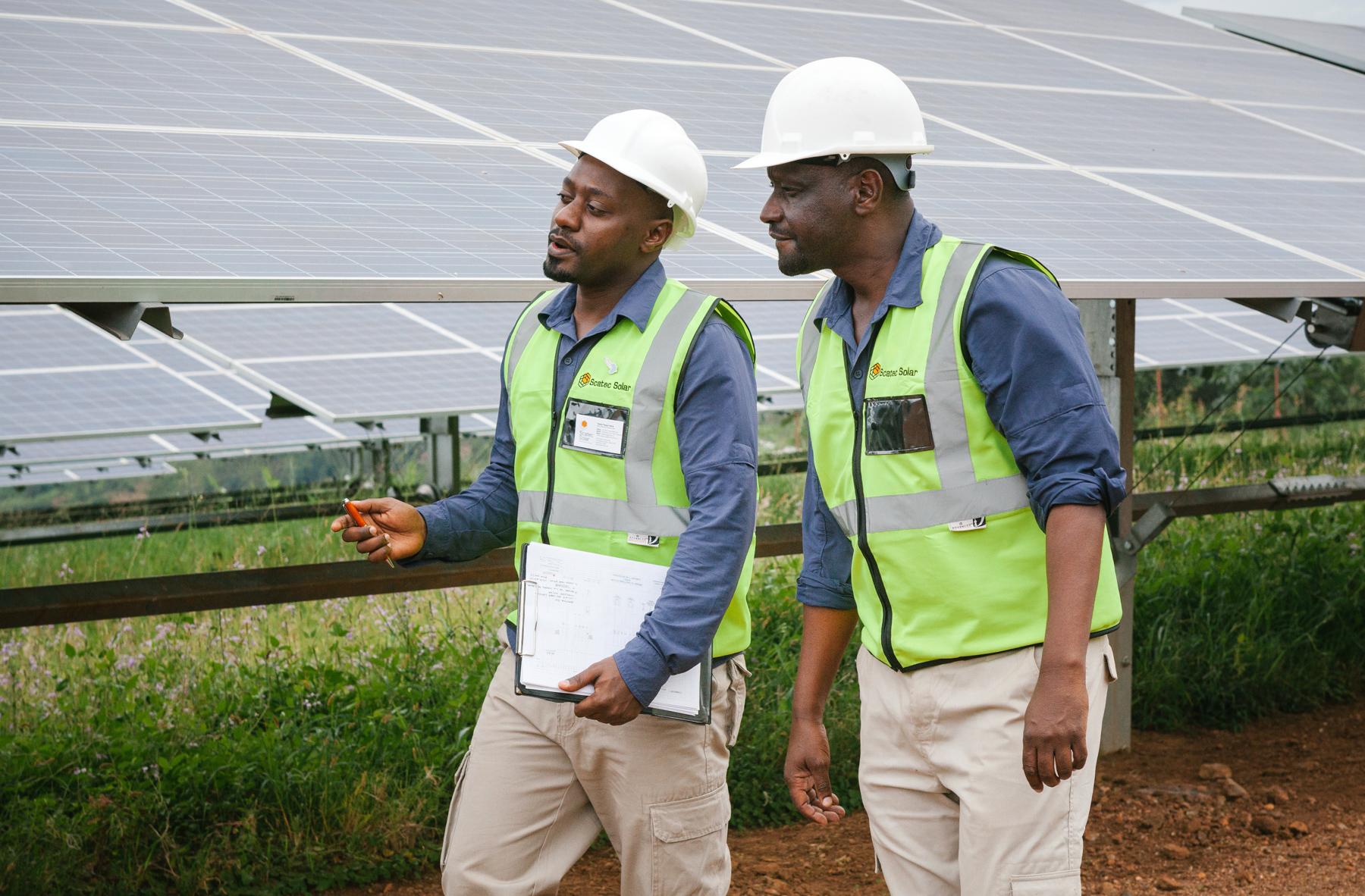 Deux ouvriers au travail avançant le long de panneaux photovoltaïques (Power Africa)