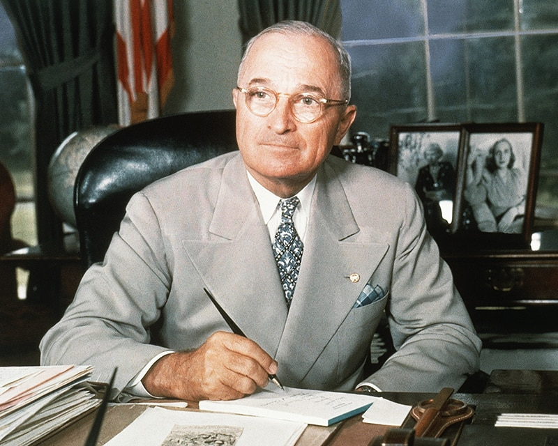 Harry S. Truman seated at desk with pen in hand (© AP Images)