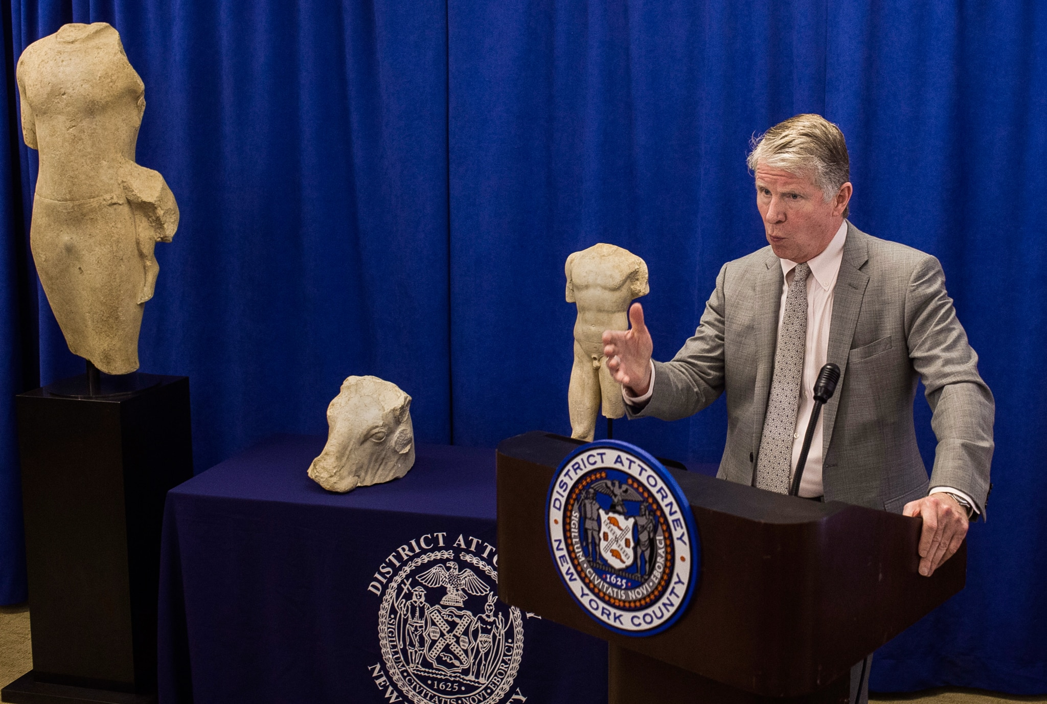 Man speaking at lectern with statues next to and behind him (© Andres Kudacki/AP Images)