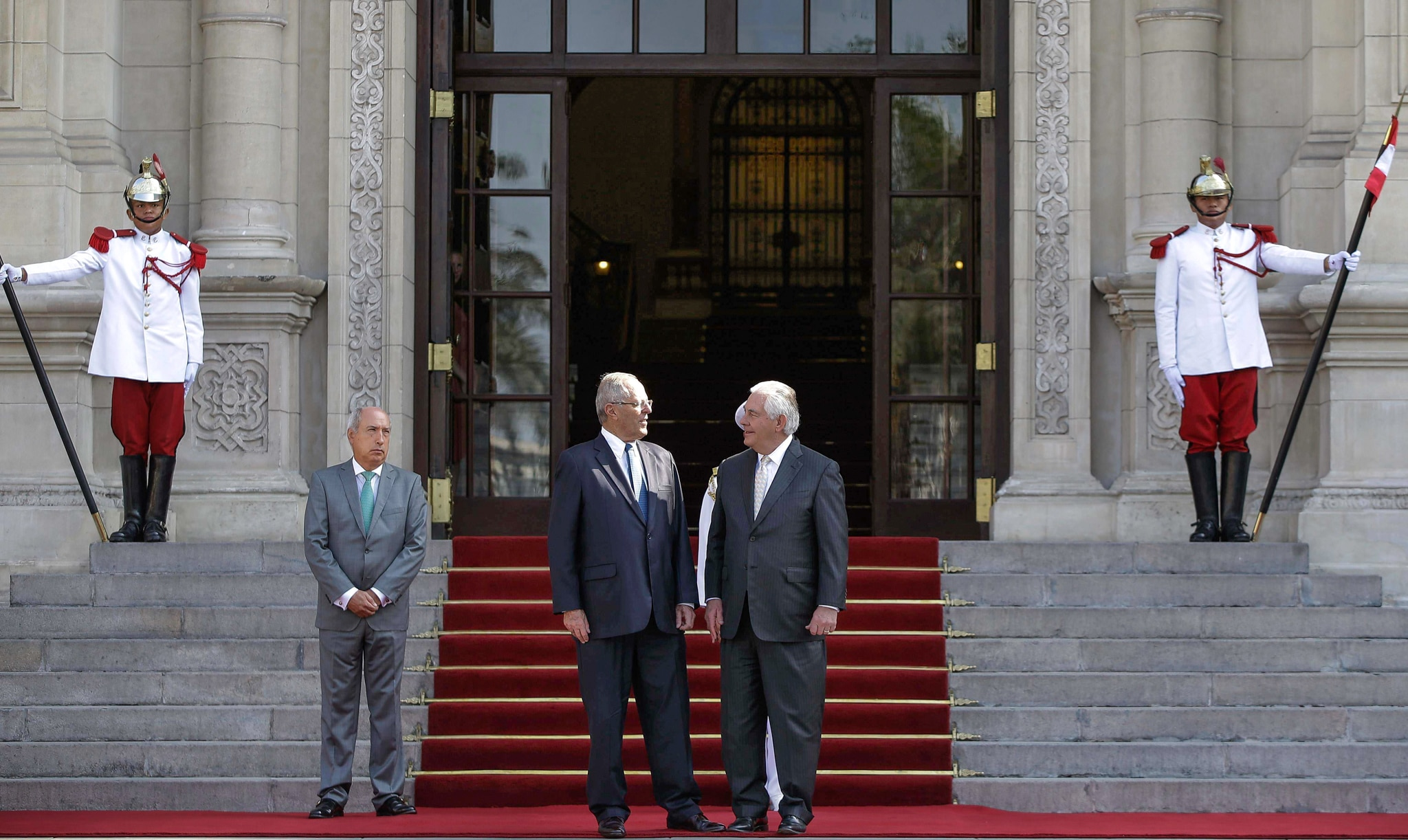 Rex Tillerson and Pedro Pablo Kuczynski standing by steps in front of building guarded by two men (© Martin Mejia/AP Images)