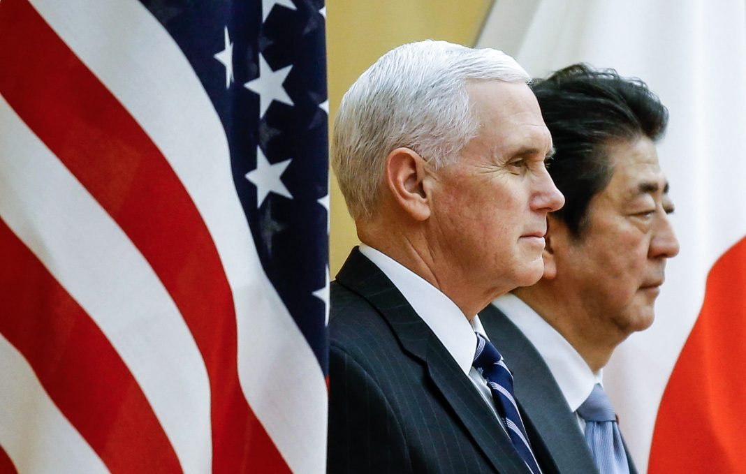 Vice President Pence and Shinzō Abe by flags (© AP Images)
