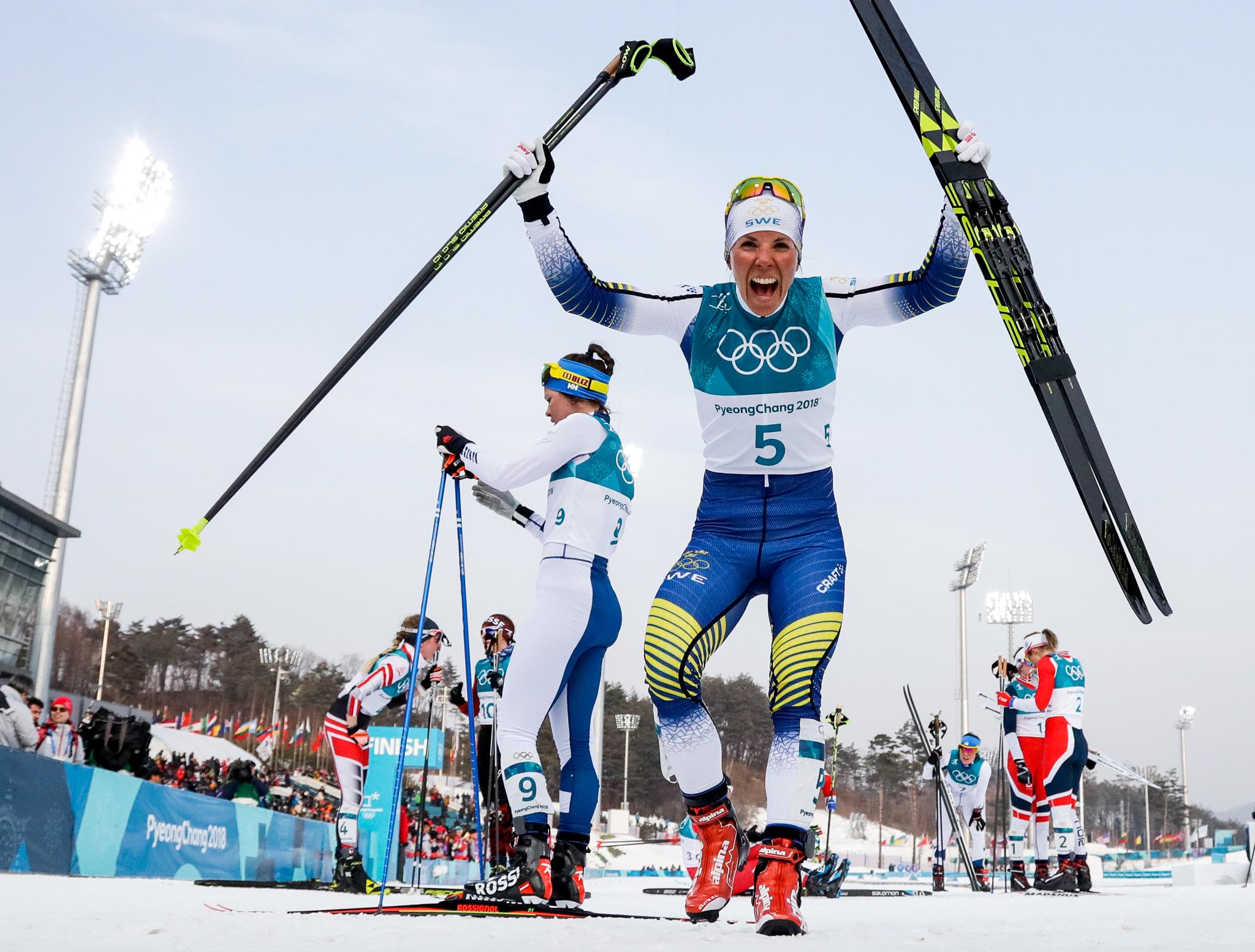 Mulher triunfante na neve segurando dois esquis (© Matthias Schrader/AP Images)