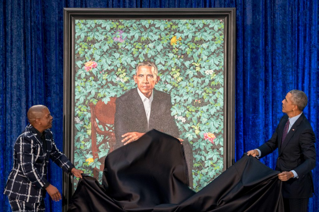 Two people removing cover from large portrait painting (© Andrew Harnik/AP Images)