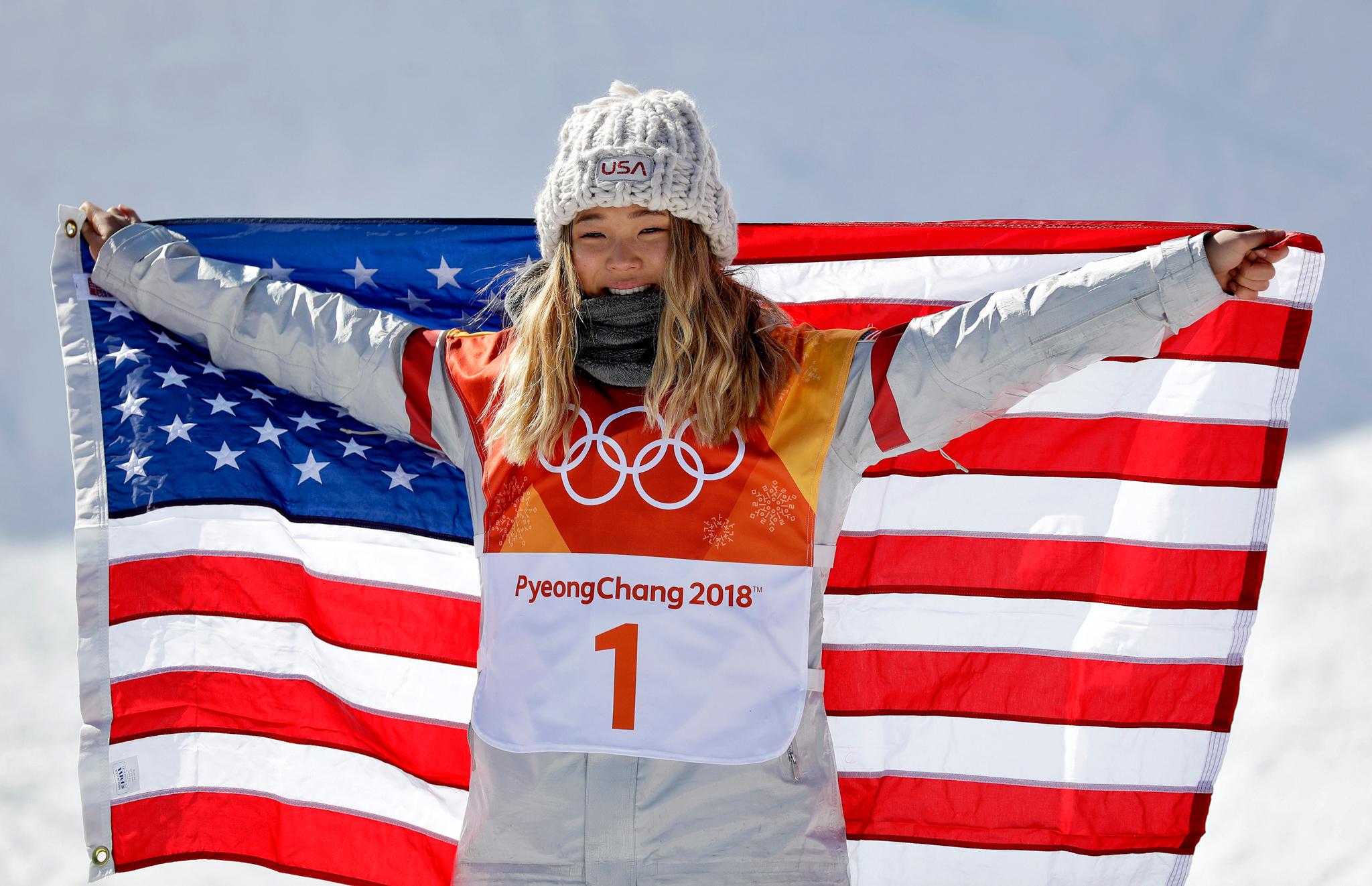 Mulher em traje de inverno segurando a bandeira dos EUA (© Gregory Bull/AP Images)