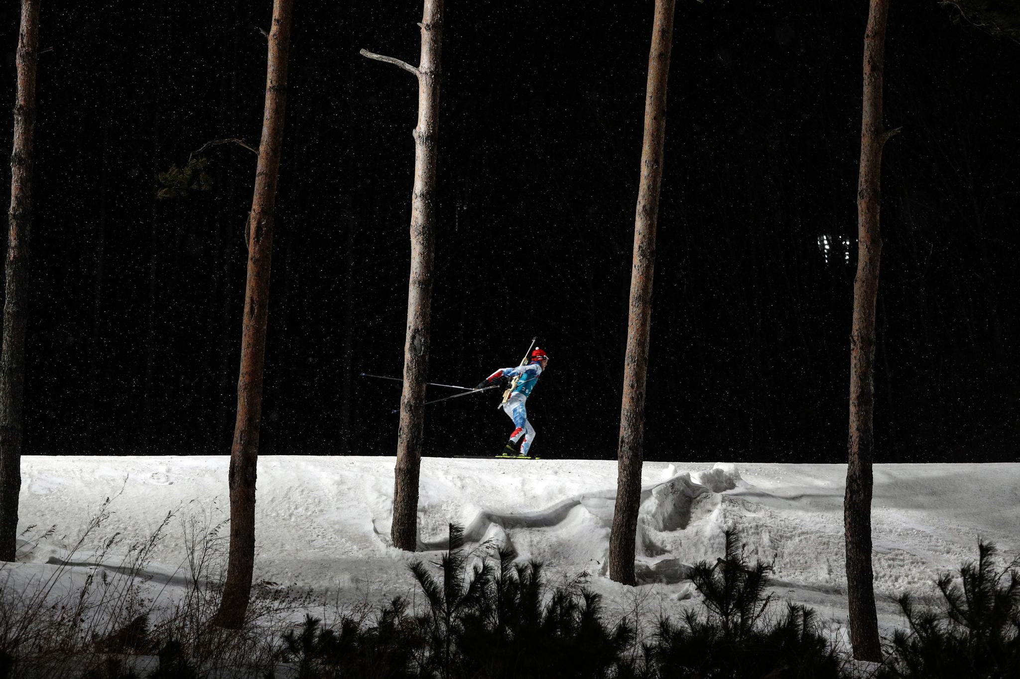 Pessoa esquiando à noite perto de fileira de árvores (© Andrew Medichini/AP Images)