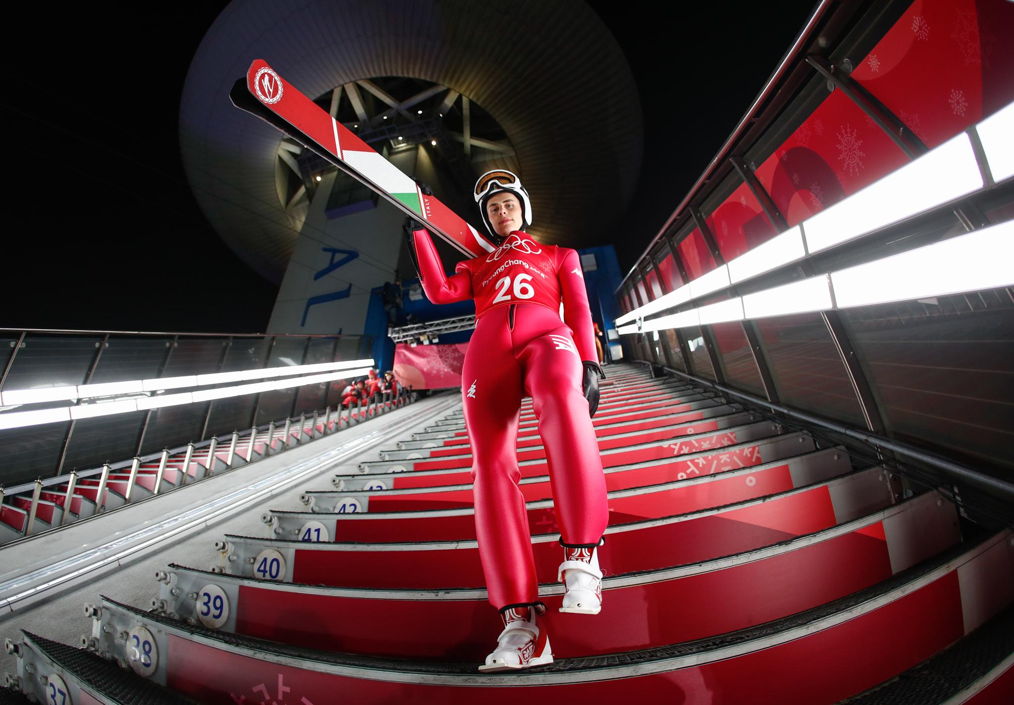 Atleta desce as escadas carregando esquis (© Matthias Schrader)/AP Images)