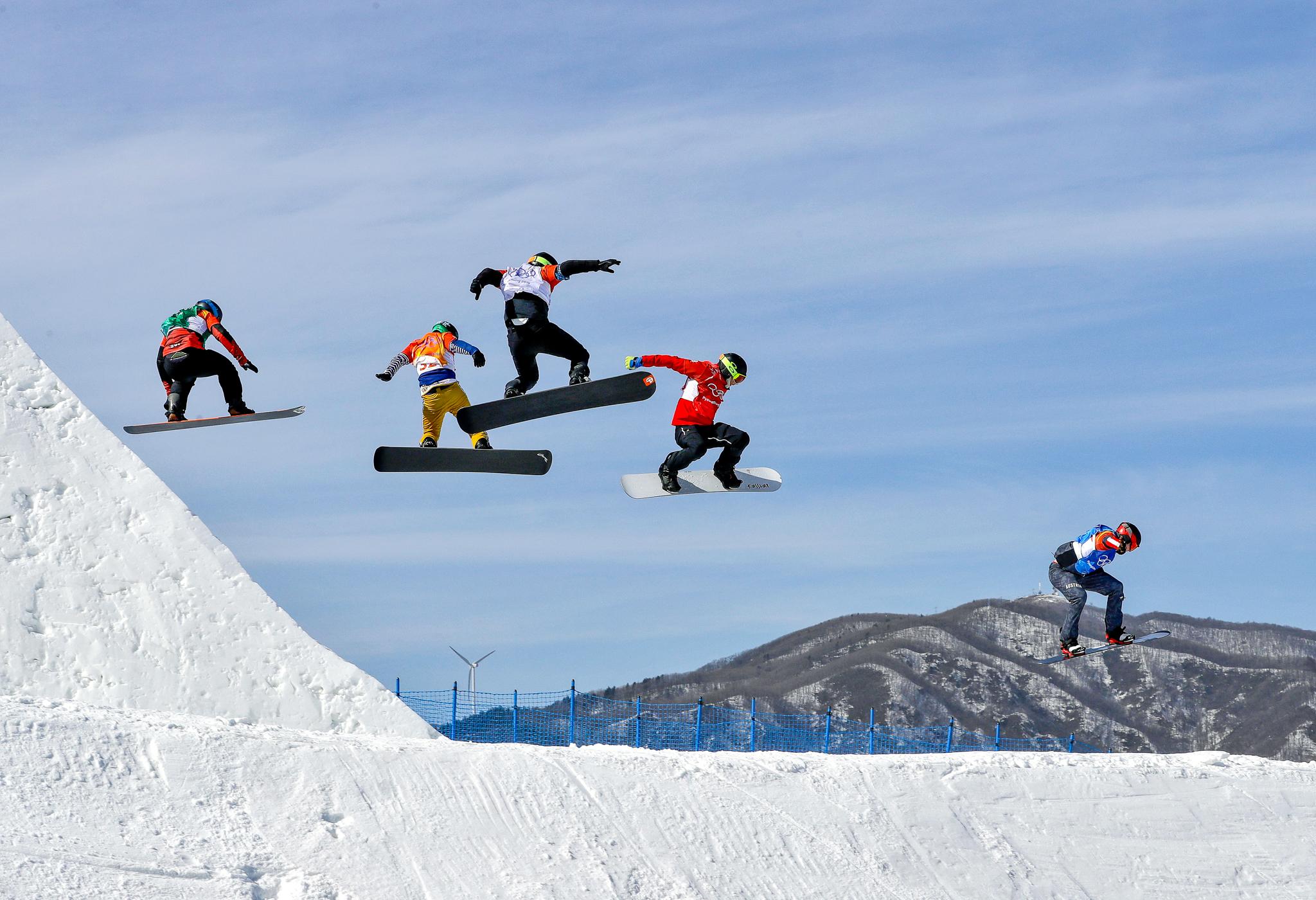 Cinco atletas de snowboard em pleno ar (© Kin Cheung/AP Images)