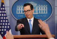 Man behind lectern pointing to raised hands (© Pablo Martinez Monsivais/AP Images)