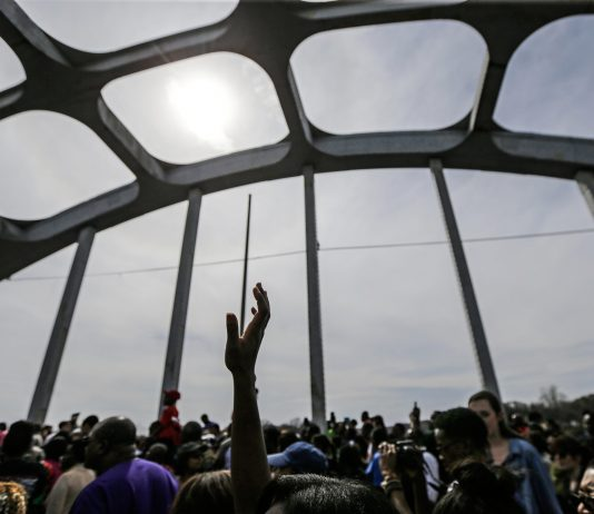 Large crowd of people on a bridge, with one hand reaching skyward (© Gerald Herbert/AP Images)