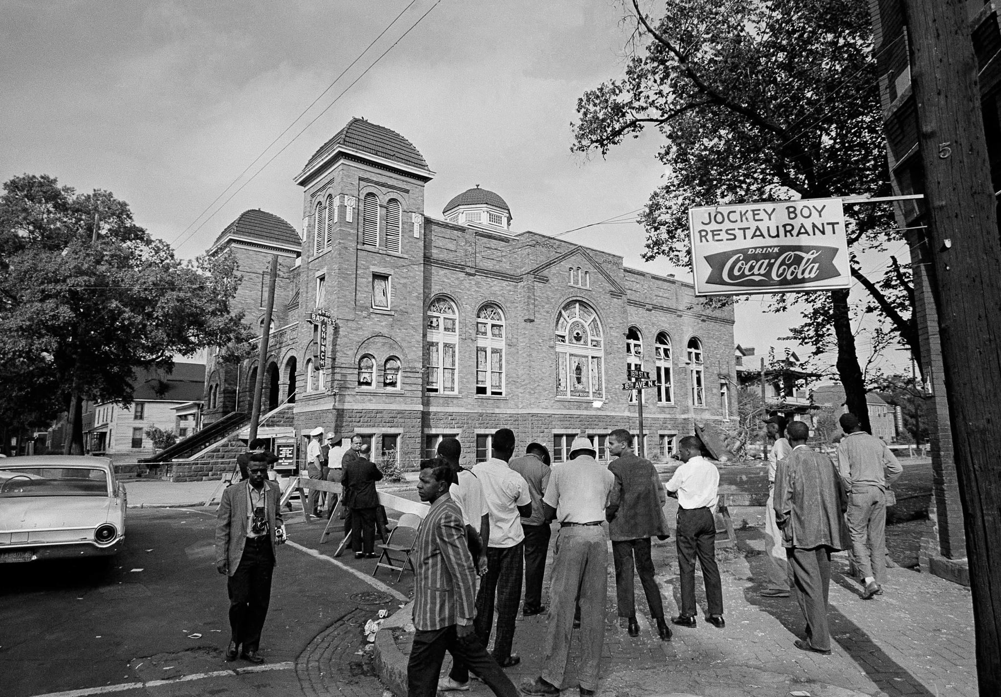 Personas de pie al otro lado de la calle frente a un edificio (Anonymous/AP Images)