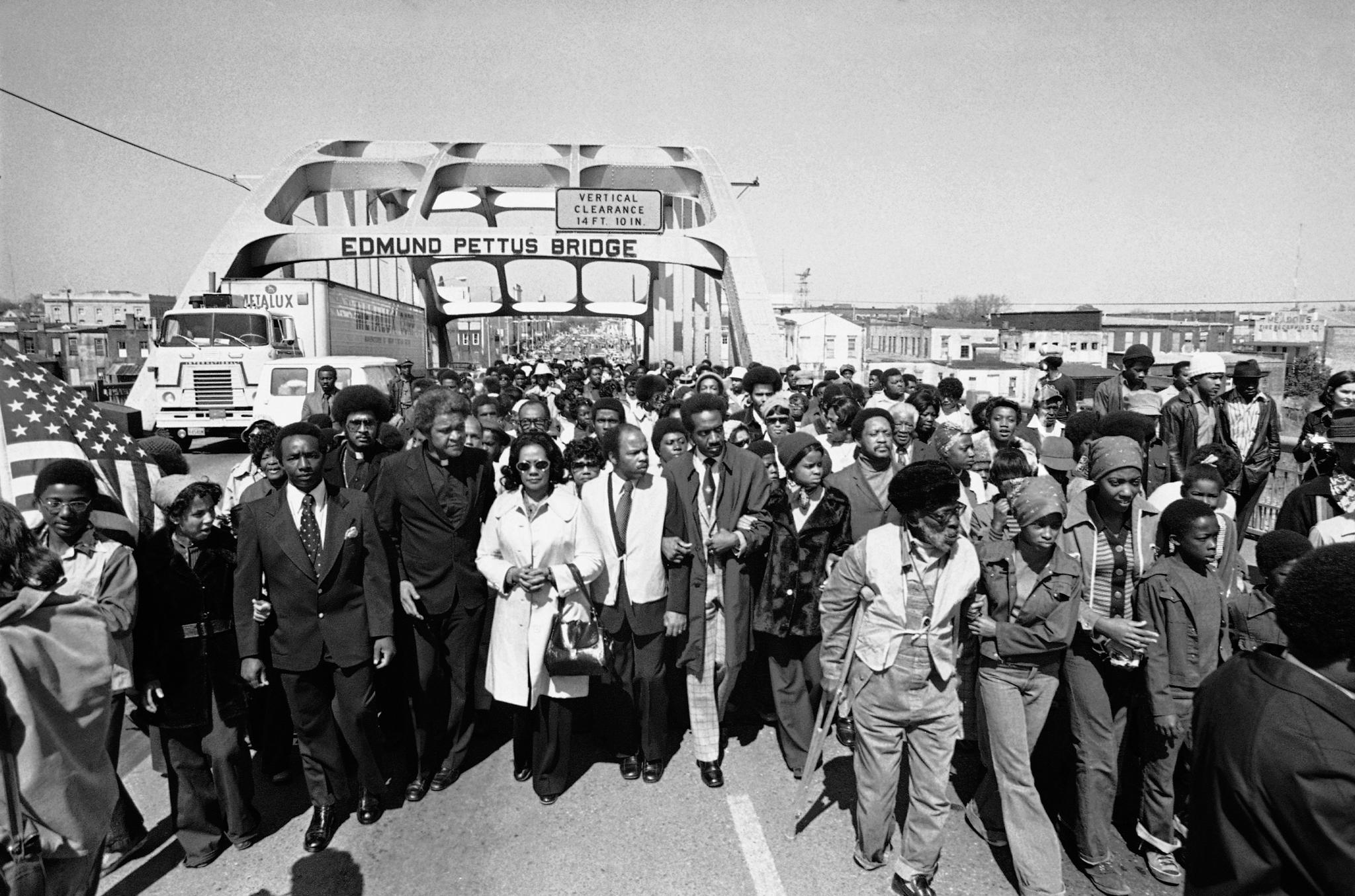 Gente marchando en un puente (Anonymous/AP Images)