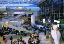 People eating at tables in large room with airplane and helicopter on display (© Bob Riha Jr/WireImage/Getty Images)