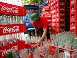 Worker stacking Coca-Cola cases filled with empty glass bottles (© Chau Doan/LightRocket/Getty Images)