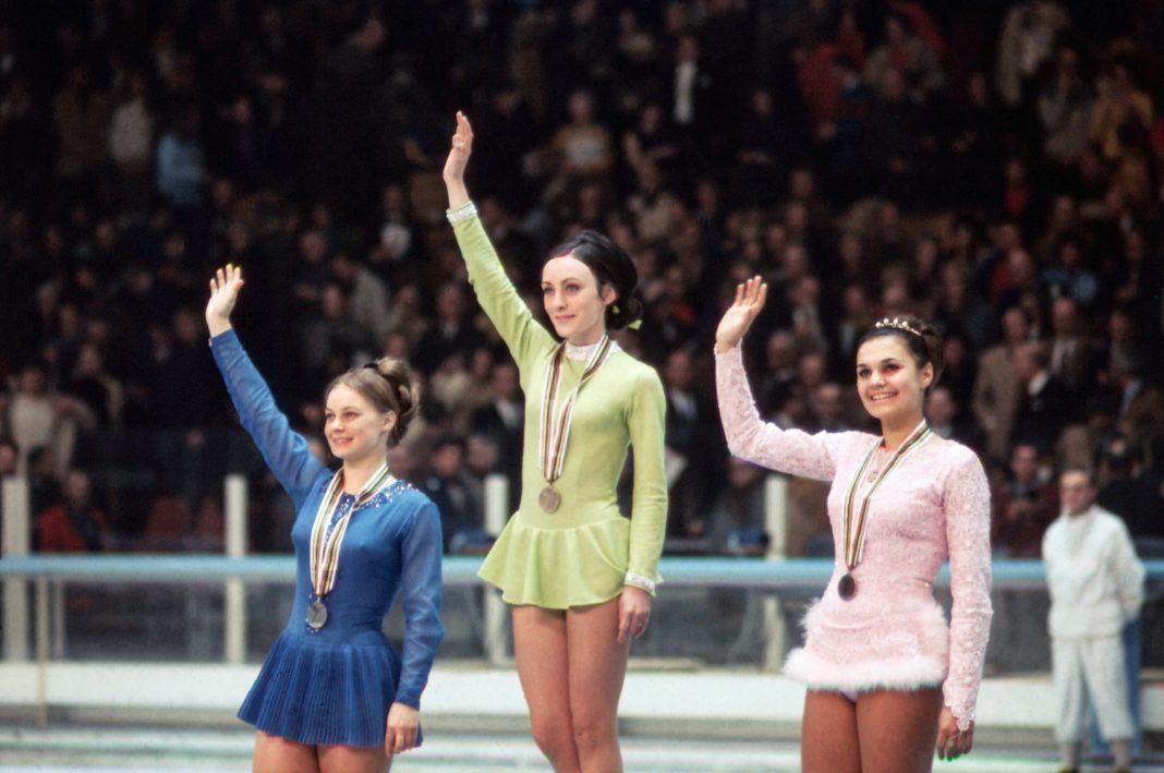Tres patinadoras artísticas con medallas saludan con la mano a la multitud (© Bettmann/Getty Images)
