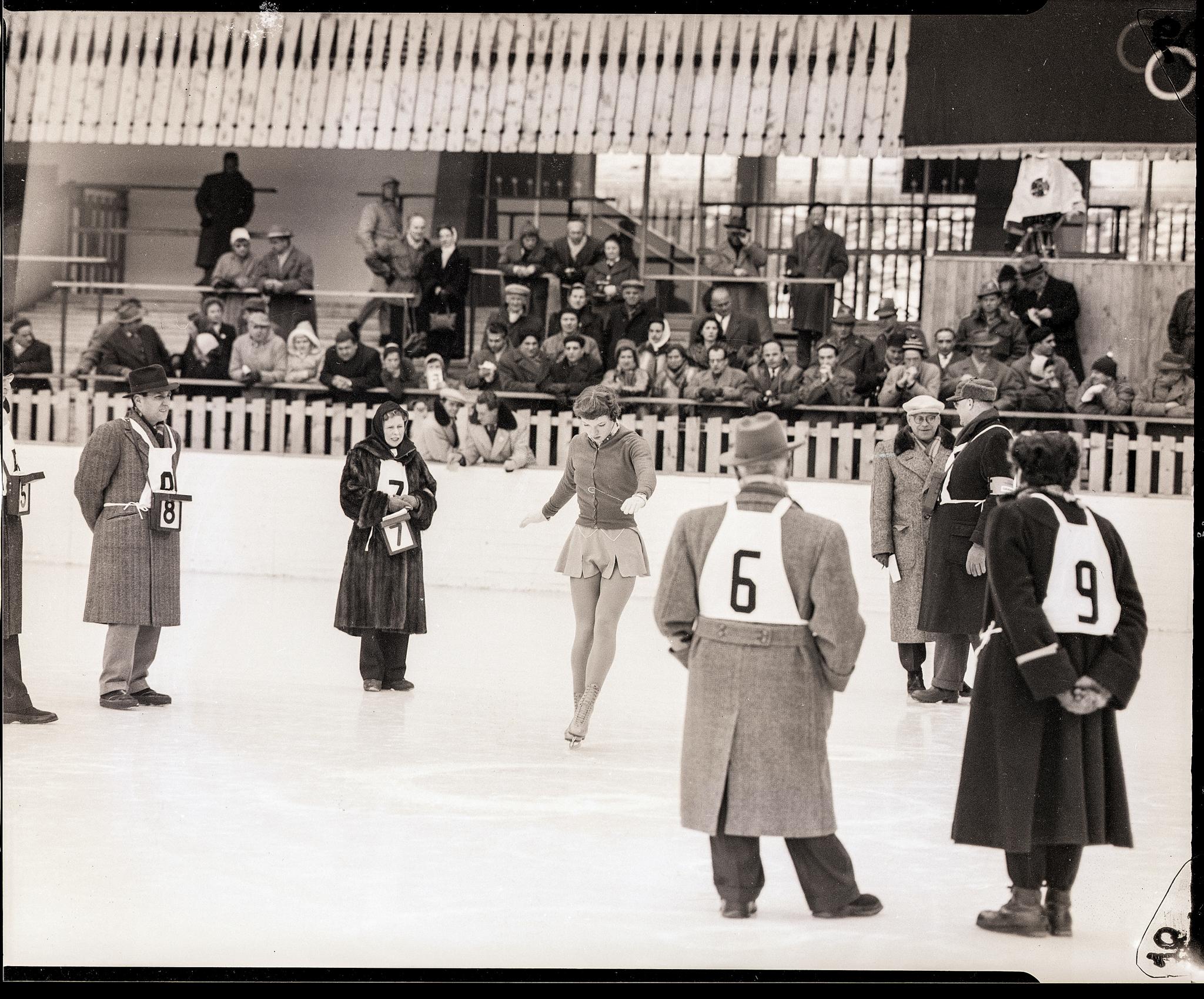Mulher executa coreografia de patinação no gelo para juízes (© Bettmann/Corbis/Getty Images)