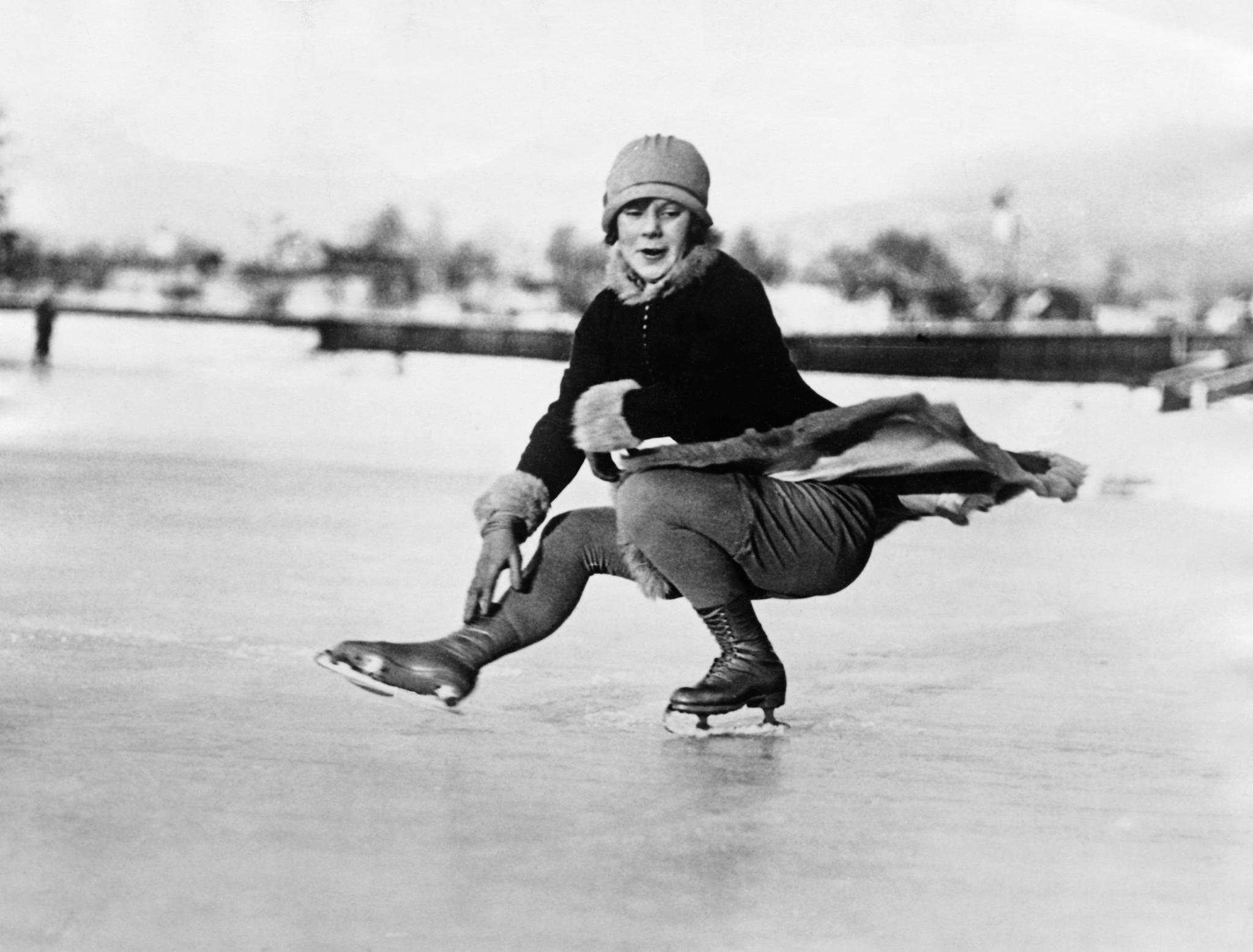 Sonja Henie em posição agachada enquanto patina (© George Rinhart/Corbis/Getty Images)