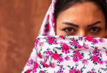 Woman wearing colorful scarf covering her face (© Corbis/Getty Images)