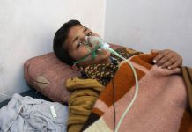 Child lying in bed with oxygen mask over face (© Mohammed Karkas/Anadolu Agency/Getty Images)