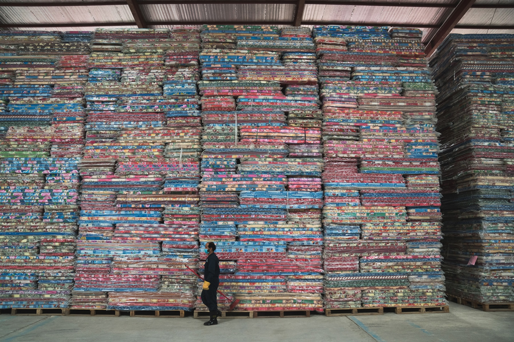 Man walking past towering piles of supplies in a warehouse (© Giles Clarke for U.N. OCHA/Getty Images)