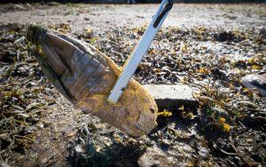 Botella de plástico sucia y dañada es recogida con tenazas (© Matt Cardy/Getty Images)