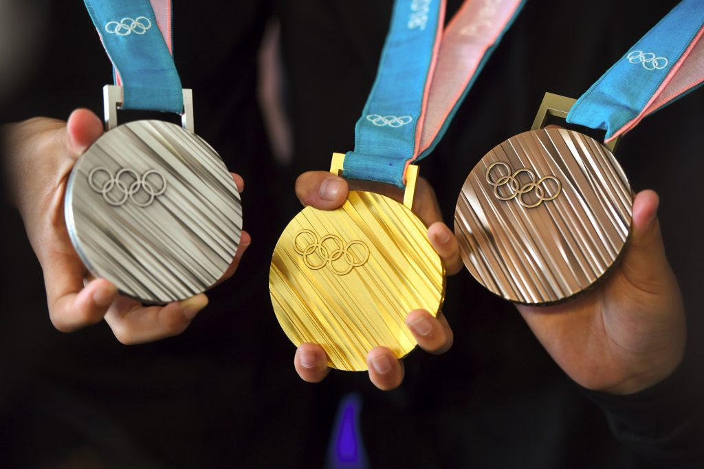 Hands holding Olympic silver, gold and bronze medals (© Jung Yeon-Je/AFP/Getty Images)